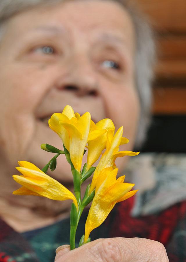 Elderly Woman Holding Flower